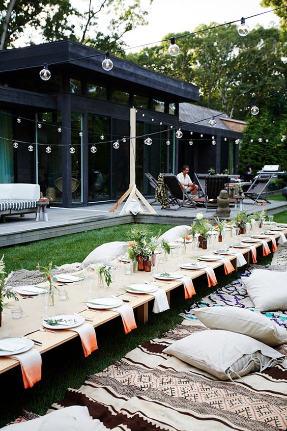 a rehearsal picnic with a low table, dyed napkins, greenery and blooms, boho rugs and pillows is casual and cool