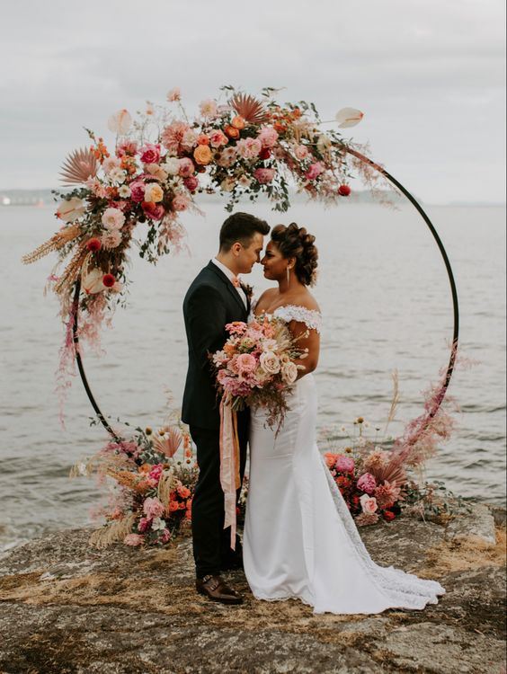 a round floral wedding arch with blush, orange, pink and hot pink blooms, pastel fronds and some greenery is chic