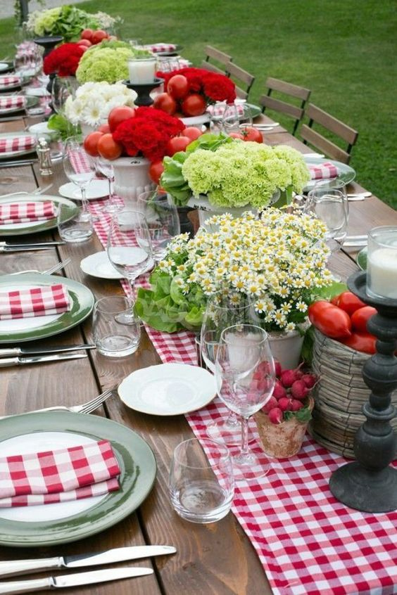 a rustic bbq rehearsal tablescape with a plaid runner and napkins, simple blooms in pots and fresh veggies and fruits in bowls
