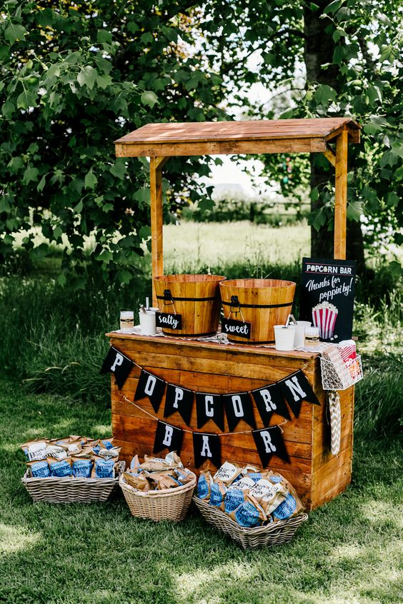 a rustic popcorn bar of stained wood, with wooden baskets for popcorn, toppings and baskets with crackers and candies
