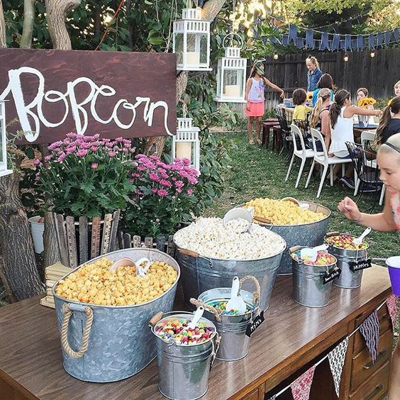 a rustic popcorn bar with buckets and bathtubs with popcorn and toppings and some potted blooms