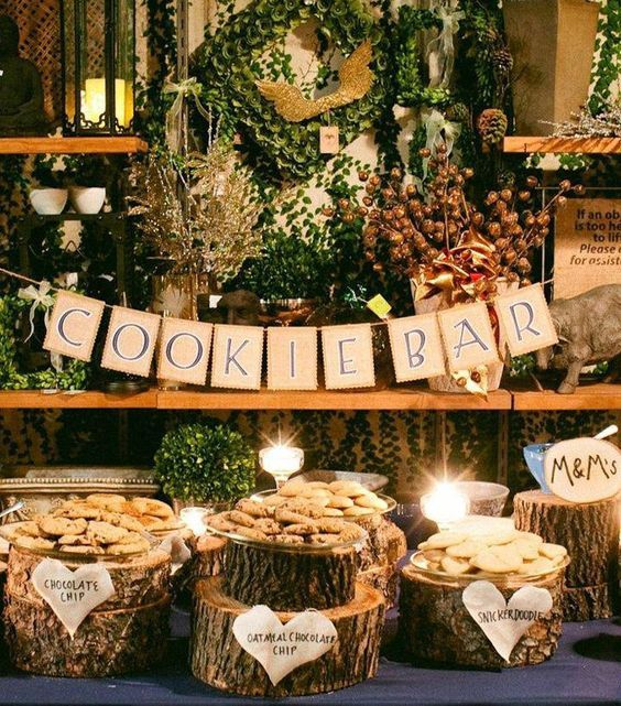 a rustic wedding cookie bar with burlap banner, wood stumps with plates wit cookies and candles around