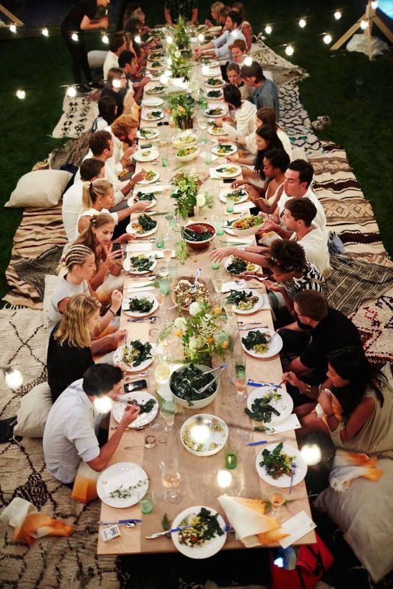 a simple boho rehearsal picnic dinner with a low table, boho rugs, boho pillows, greenery and candles