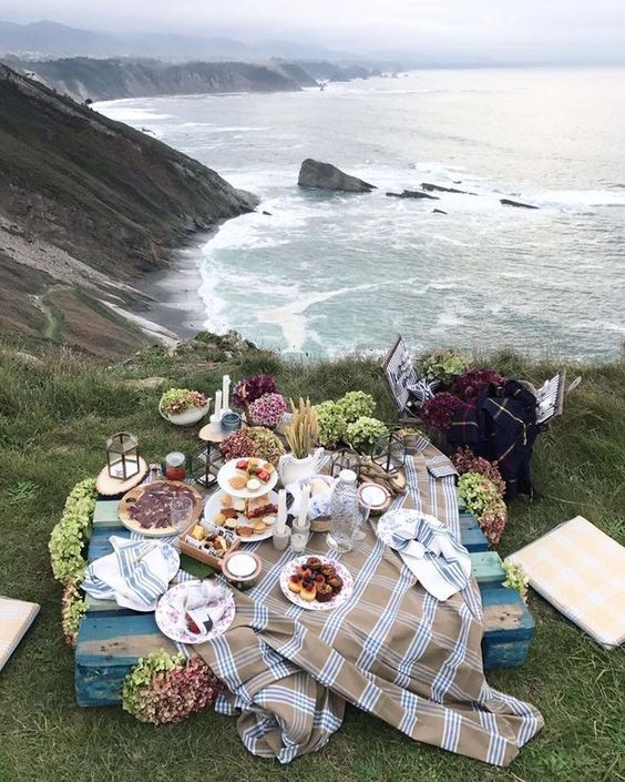 a simple rustic picnic setting with a lwo wooden table, plaid textiles, some hydrangeas, candles and lots of food