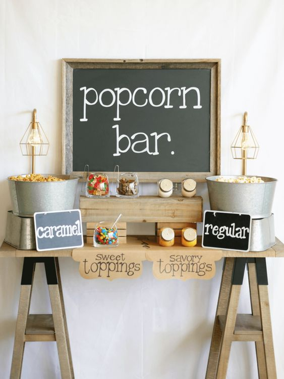 a simple rustic popcorn bar with chalkboard signage, popcorn in buckets, colorful sprinkles in jars
