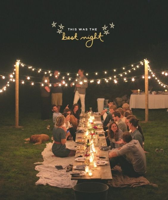 a simple rustic rehearsal dinner picnic with a low table, candle lanterns, lights and blooms is a cozy event