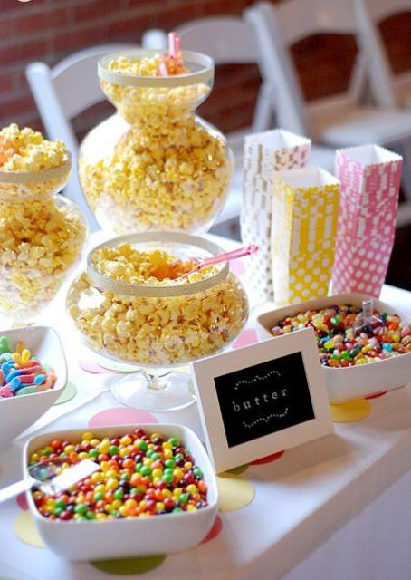 a small and cute popcorn bar with popcorn in glass jars, sprinkles and candies and colorful paper bags