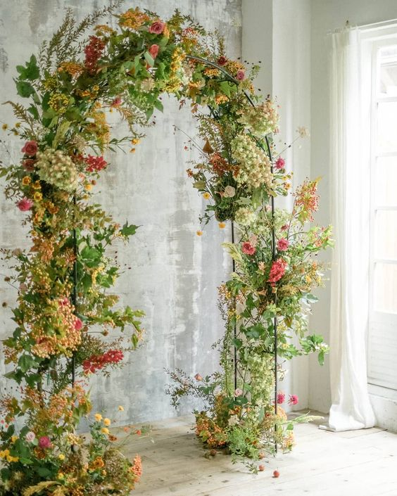 a sophisticated fall wedding arch done with greenery and foliage and bright yellow, orange and pink blooms is amazing