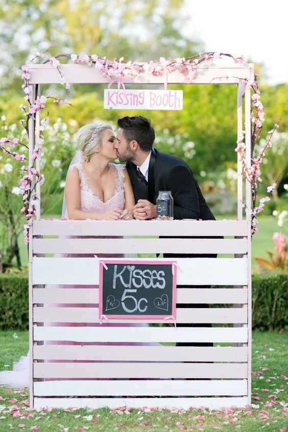 a spring-like kissing booth of white wood, with pink and white cherry blossom and with a chalkboard sign