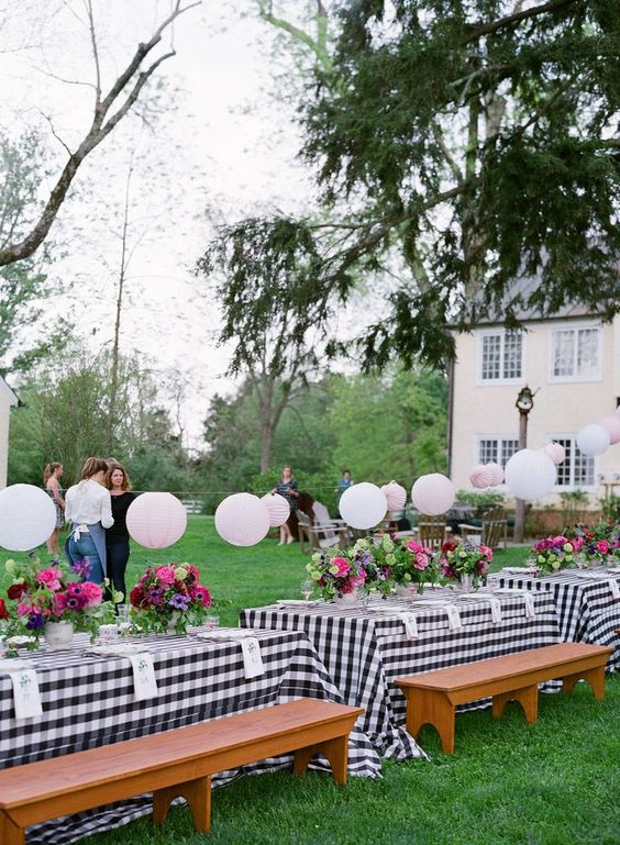 a stylish bbq rehearsal dinner reception with plaid tablecloths, pastel paper lamps, bright florals and greenery