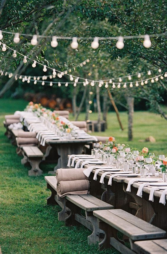 a stylish bbq rehearsal reception with lights over it, benches with burlap covers, bright blooms, neutral linens