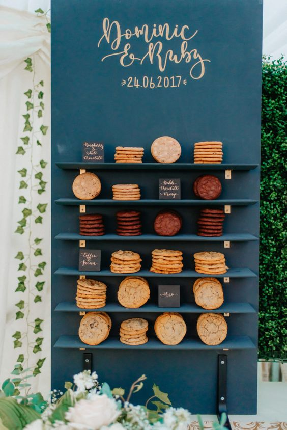 a stylish navy cookie wall with shelves nd various types of cookies, each marked with a little sign