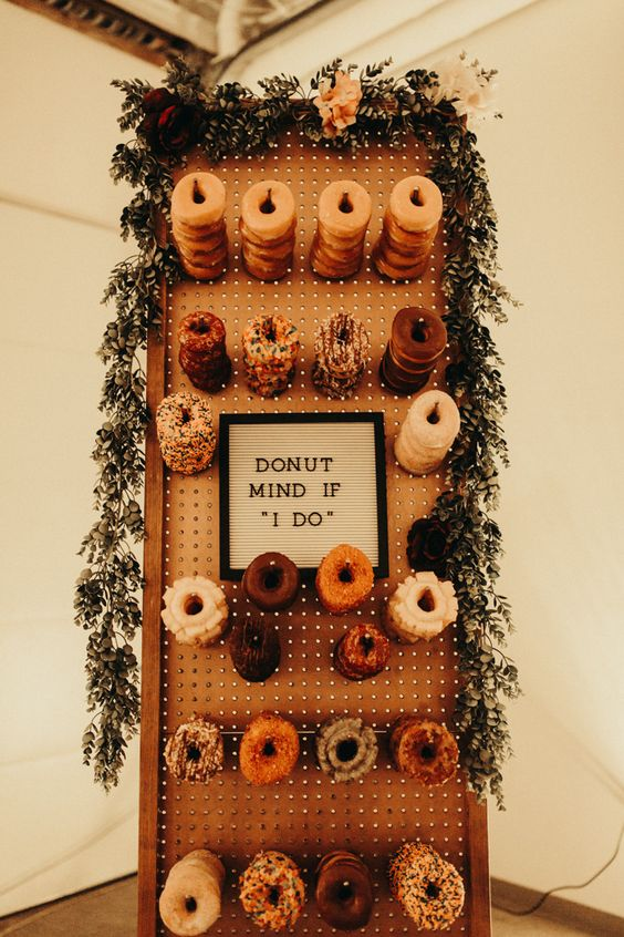 a stylish pegboard wall with holders and glazed donuts, with a sign and greenery and bloom garland on top