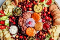 a summer burger board with sliders, various vegetables, cherries, French fries, various dips and meat looks epic