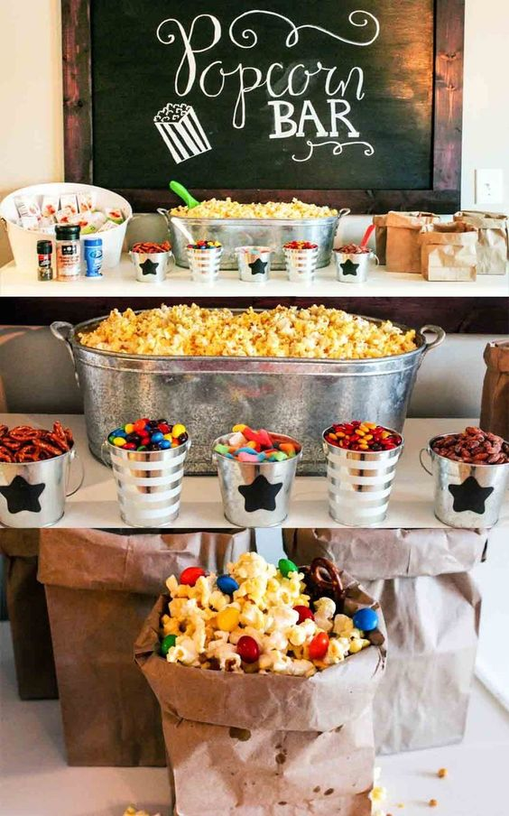 a super bright and fun popcorn bar with buckets and bathtubs, lots of colorful popcorn and candies and paper bags for serving