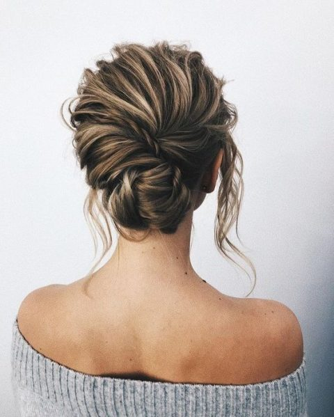 a textured messy twisted and braided low updo with locks down for a modern romantic bride