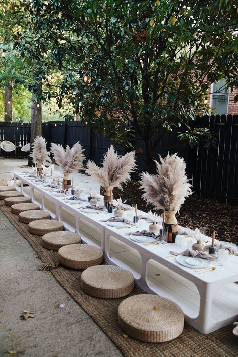 a trendy neutral boho picnic with pampas grass, candles, pastel and neutral textiles and jute ottomans