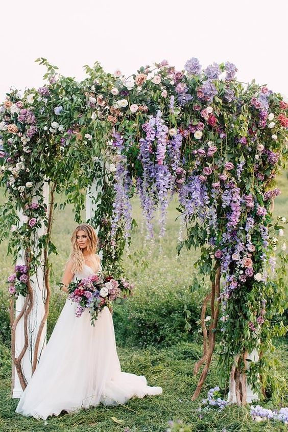 a very natural wedding arch with much greenery, purple and light pink blooms and some neutral fabric is wow