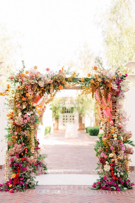 a vibrant floral wedding arch decorated with pink, rust, yellow, orange and deep red blooms, greenery and foliage is amazing