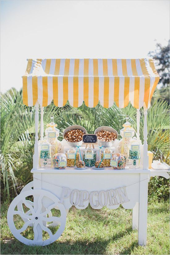 a vintage popcorn bar cart with colorful popcorn, nuts and candies in glass jars of various sizes and shapes
