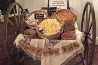a vintage trolley popcorn bar with a lace blanket, a burlap banner, popcorn in wooden baskets and chalkboard signs