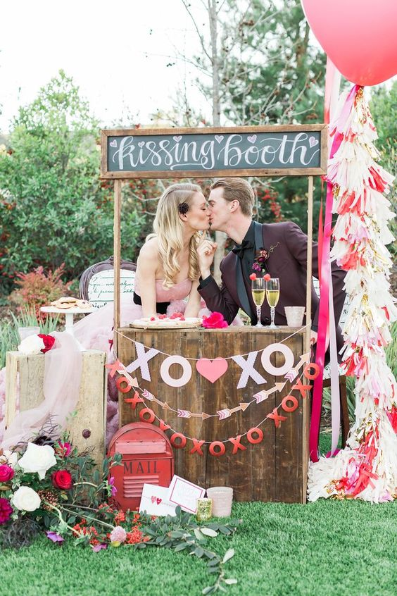 a whimsy and playful wedding kissing booth of wood, with a chalkboard sign, paper banners and with blooms around
