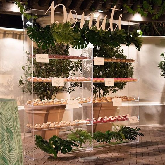 an acrylic donut wall with shelves with lush tropical greenery for a modern wedding