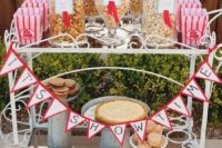 an elegant vintage popcorn cart with a banner, popcorn in jars, cupcakes and pies and paper bags