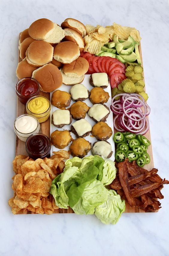 build your own burger bar board with burgers, vegetables, French fries, greenery, sauces and dips