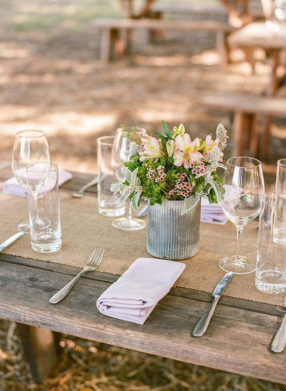 simple rustic tablescape styling with uncovered tables, a burlap runner, blush blooms and greenery in a tin can and silver