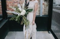 a 1920s inspired wedding dress with an embellished bodice, cap sleeves, an illusion neckline and emerald velvet heels