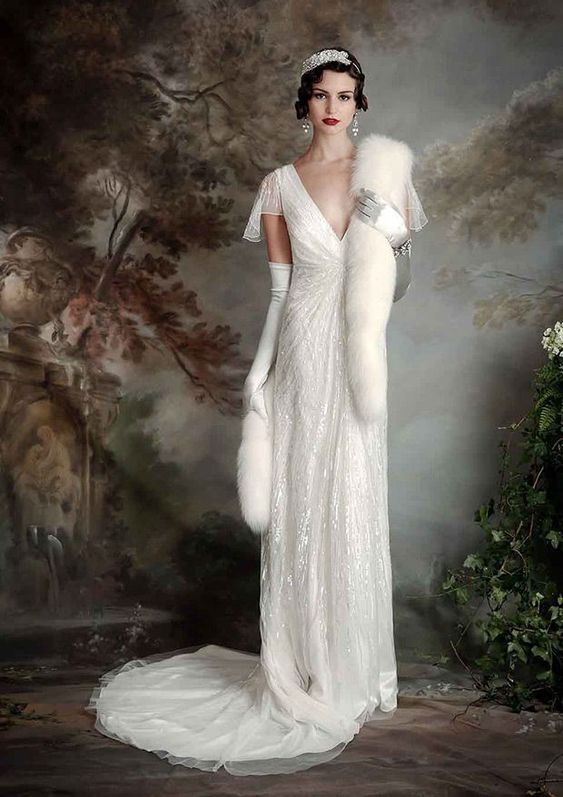 a 1920s inspired white sheath wedding dress with draperies, embellishments, cap sleeves and a train plus faux fur and tall gloves