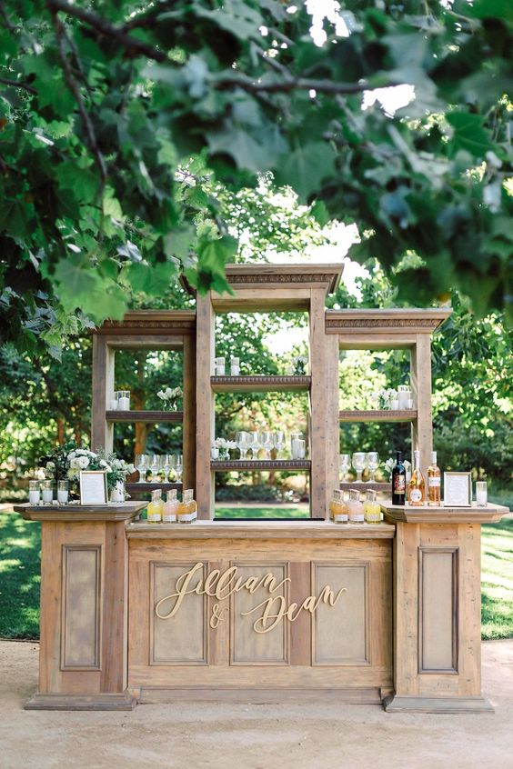 a beautiful and stylish wooden drink bar with open shelves, calligraphy and a greenery and white floral arrangement is veyr chic
