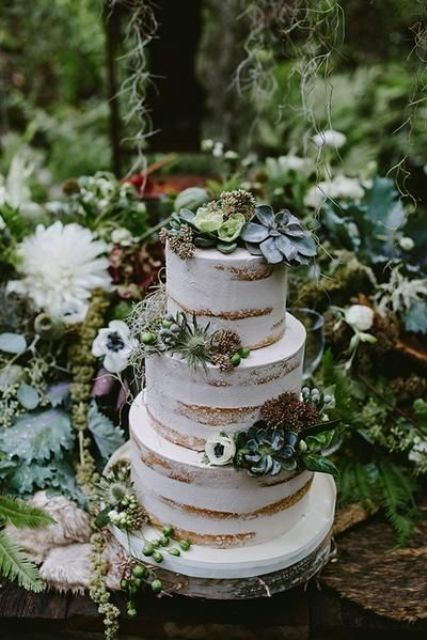 a beautiful naked wedding cake decorated with neutral blooms, greenery and succulents