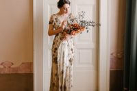 a beautiful sheath embellished wedding dress with gold beading, short sleeves, a V-neckline and a train