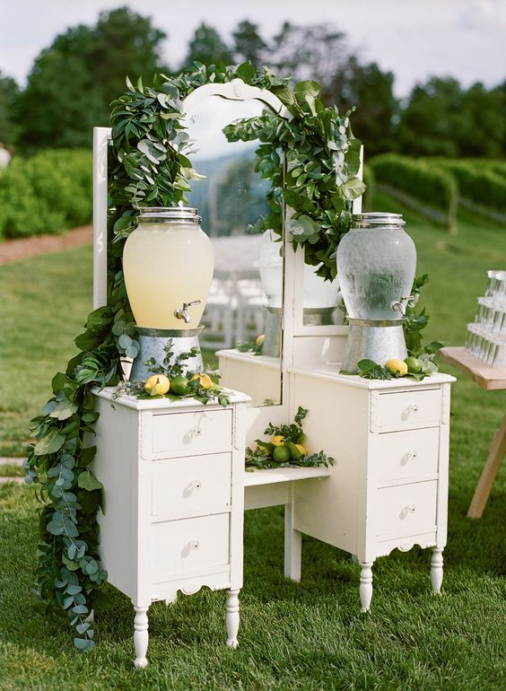 a beautiful vintage drink bar of a vintage vanity, with drawers and lemonade on stands, with greenery and citrus is a veyr cool idea