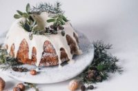 a bundt wedding cake with white chocolate dripping, evergreens, pinecones and sugar powder to imitate snow