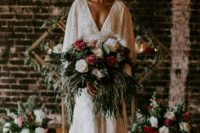 a chic art deco wedding gown with a plunging neckline, cape, train and floral embellishments