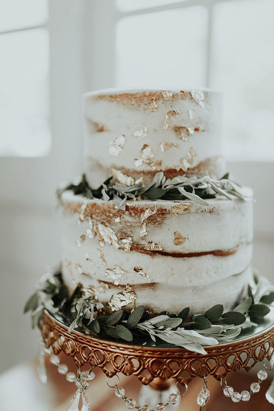 a chic naked wedding cake with gold leaf and greenery for a cute rustic or modern wedding