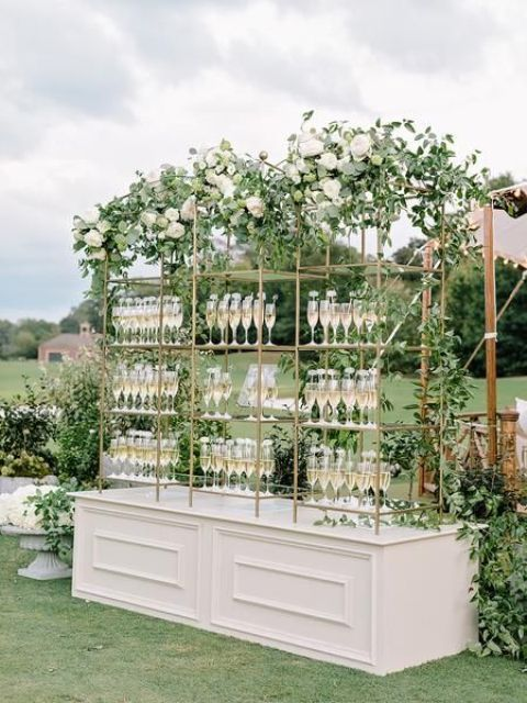 a chic wedding drink bar with gilded stands with drinks and lots of greenery garlands and white blooms is a beautiful idea