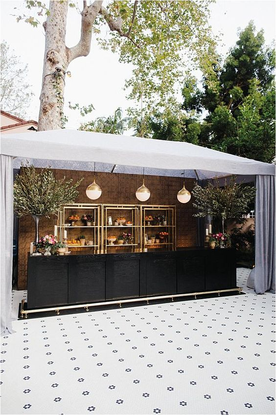 a cool glam wedding drink bar with a black bar stand, with gilded open shelves, potted trees and bubble glass pendant lamps