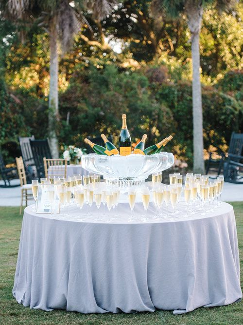 a creative and chic wedding drink bar of a round table, a crystal bowl with bottles and glasses is a lovely solution to rock