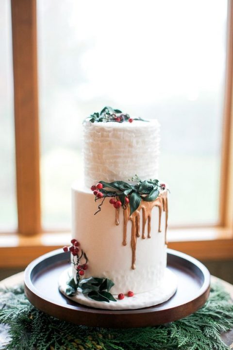 a frosted wedding cake with a ruffled layer, gold drip and mistletoe for a winter or Christmas wedding