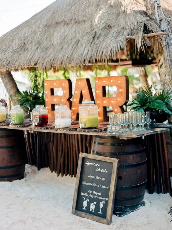 a gorgeous tropical wedding bar with a roof, a stand of stained wood and barrels, a marquee sign and tropical leaves is amazing