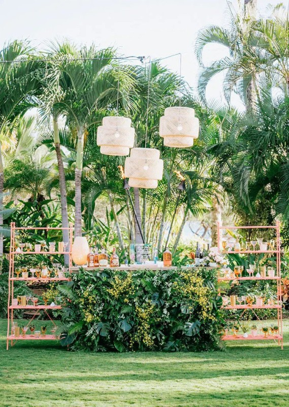 a gorgeous tropical wedding drink bar of a stand covered with fall leaves and wihte blooms, with pink open shelving units and woven pendant lamps