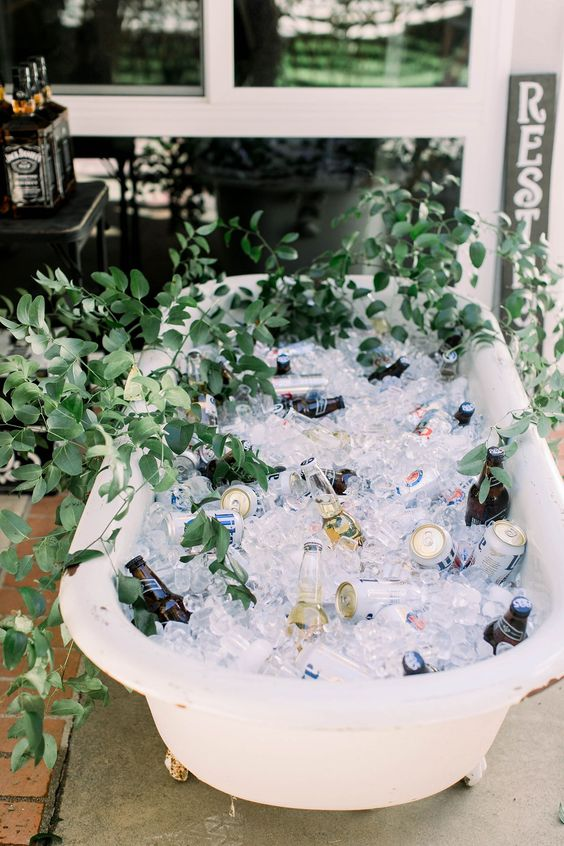 a lovely and simple drink bar alternative - a bathtub filled with ice and greenery and lots of drinks in tin cans and bottles is a cool idea