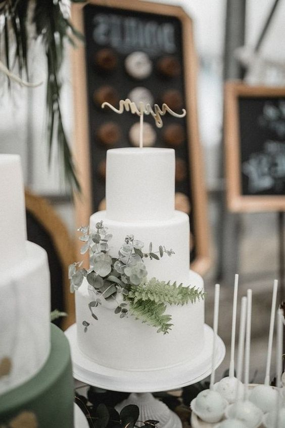 a modern white wedding cake with eucalyptus and ferns plus a topper is a chic idea