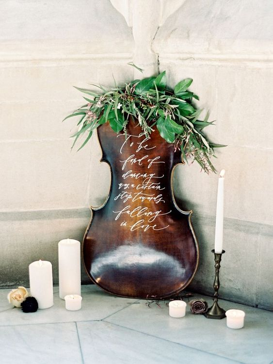 a musical instrument dressed up with greenery can substitute any usual sign and make your wedding decor more special