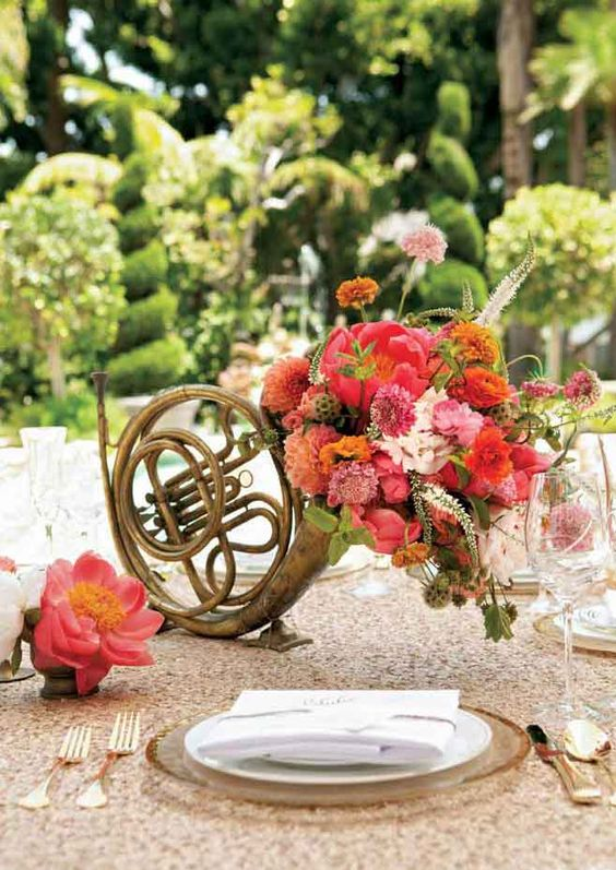 a musical instrument filled with colorful blooms and greenery is a beautiful and really unique wedding centerpiece
