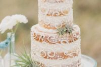 a naked wedding cake with cream decor and airplants is a great idea for a coastal or beach wedding